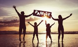 Happy family jumping on the beach at the sunset time.