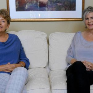 2 women sitting on couch
