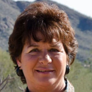 susan woman with short brown hair in front on mountains