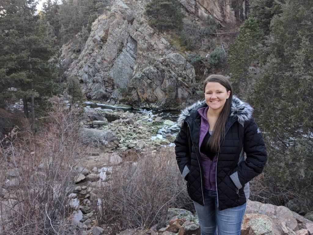 girl in black winter coat next to river