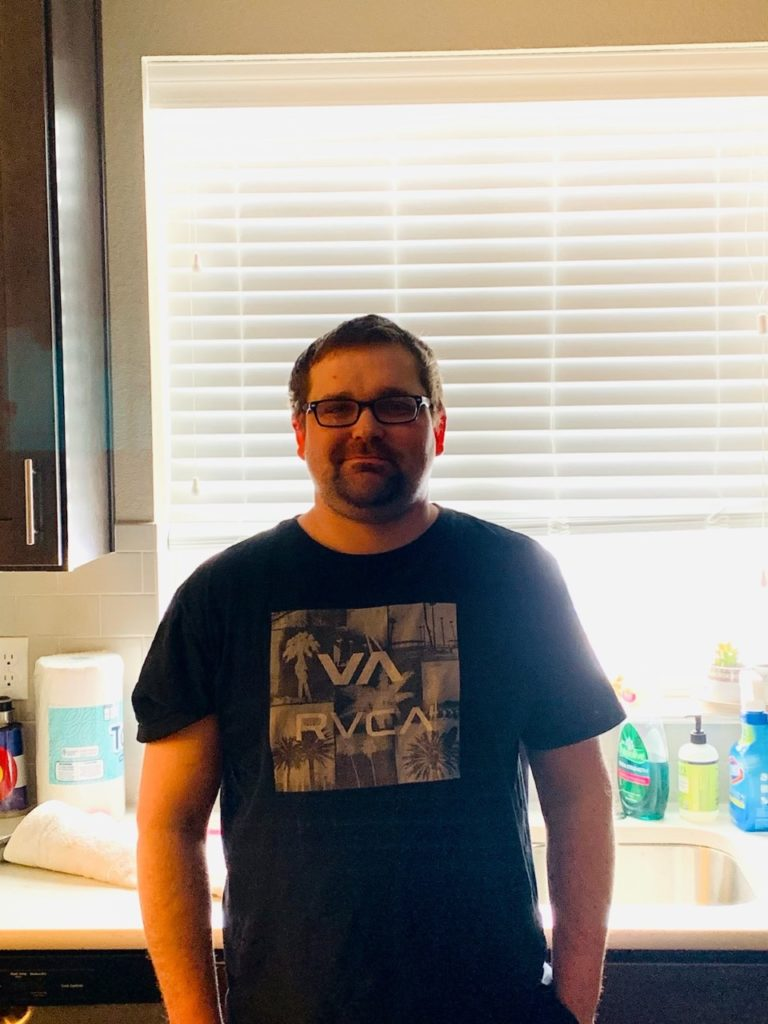 pat guy with glasses standing in kitchen