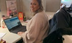 blonde girl in pink sweater sitting at desk
